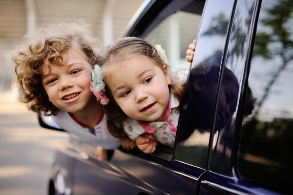 two kid lean heads out of the car window