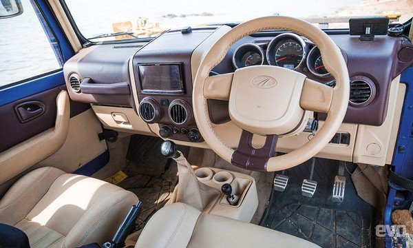 Mahindra Thar Wanderlust's front cabin space, beige-coloured interior, being displayed in showroom