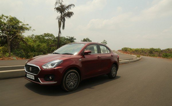 Diagonal right side view of Maruti Dzire, red Dzire running on tarmac road