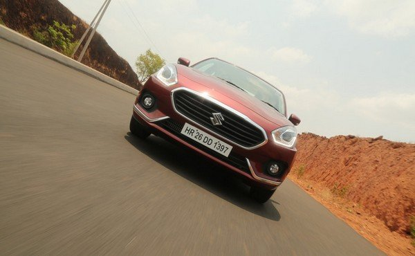 Front view of Maruti Dzire; red Dzire running on tarmac road