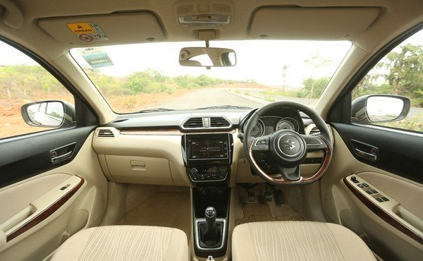 red Maruti Dzire's behind-the-wheel view in the cabin; Dzire running on road