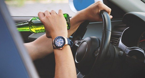 driver drinking while operating vehicle, one human hand holding alcohol bottle, the other holding the steering wheel