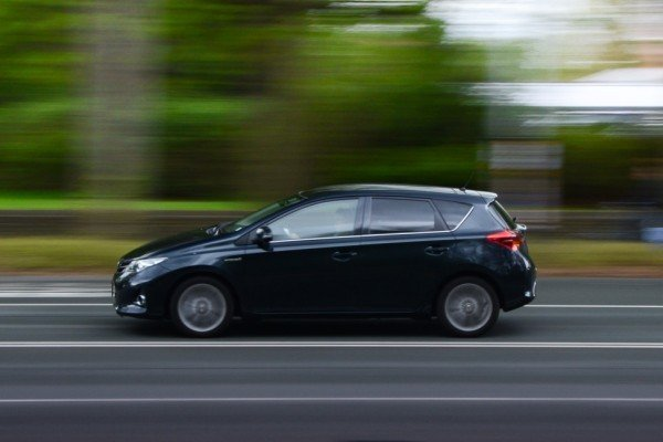 black hatchback running on road, right sideways view, blurry background of trees