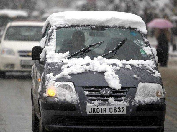 A black car covered with snow during a snowfall