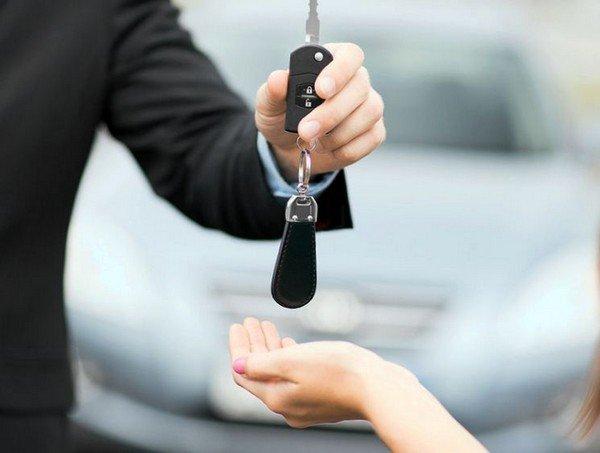 a man hands a girl a car key