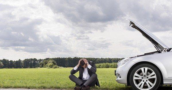 A miserable man is sitting beside a broken car