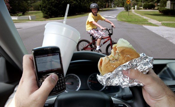 Someone texting and eating while driving