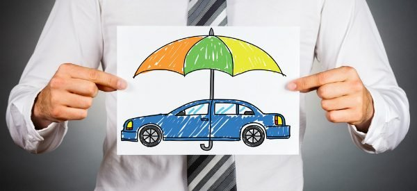 a man holding a picture of a car under an umbrella