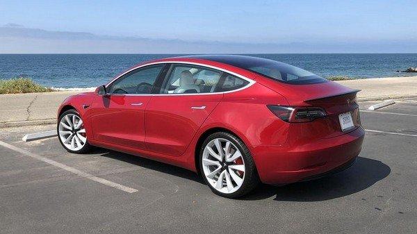 Tesla model 3, red colour, rear angular look