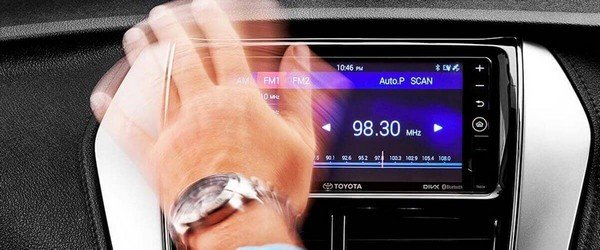hand waving in front of car dashboard