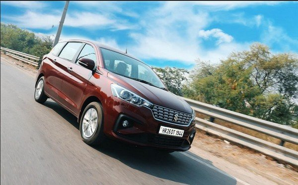Maruti Ertiga red color running on road from left to right