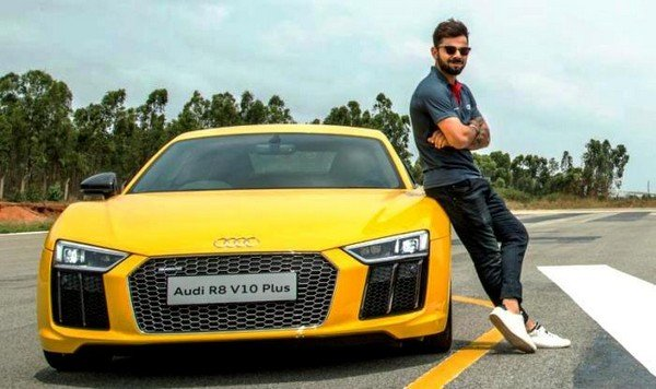 Virat Kohli standing next to a yellow Audi A8