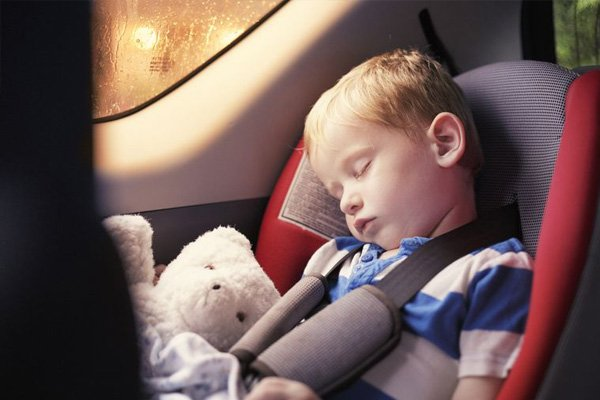 a child is sleeping at the back seat