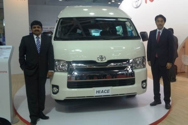 Toyota Hiace pickup truck white front between two men