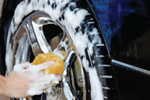 man using a sponge to clean wheels