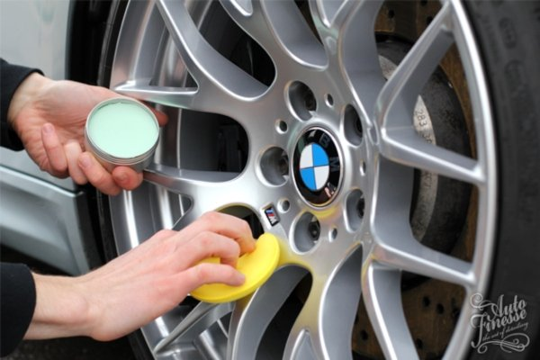 man applying sealant to car wheel