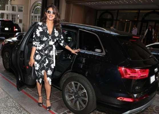 Priyanka Chopra smiling standing next to her black Audi Q7