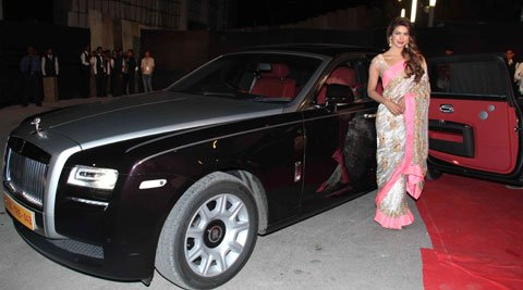 Priyanka Chopra wearing sari standing next to her Rolls-Royce