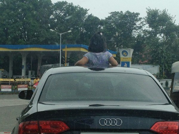 kid sticking out of car sunroof