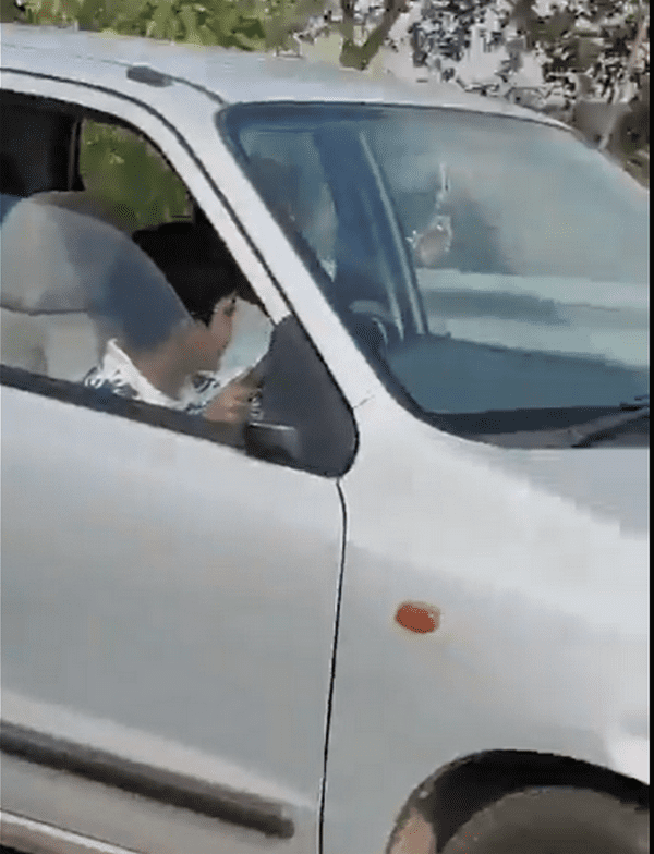 Side angle shot of the kid driving a car