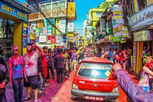 A car on a Holi festival street