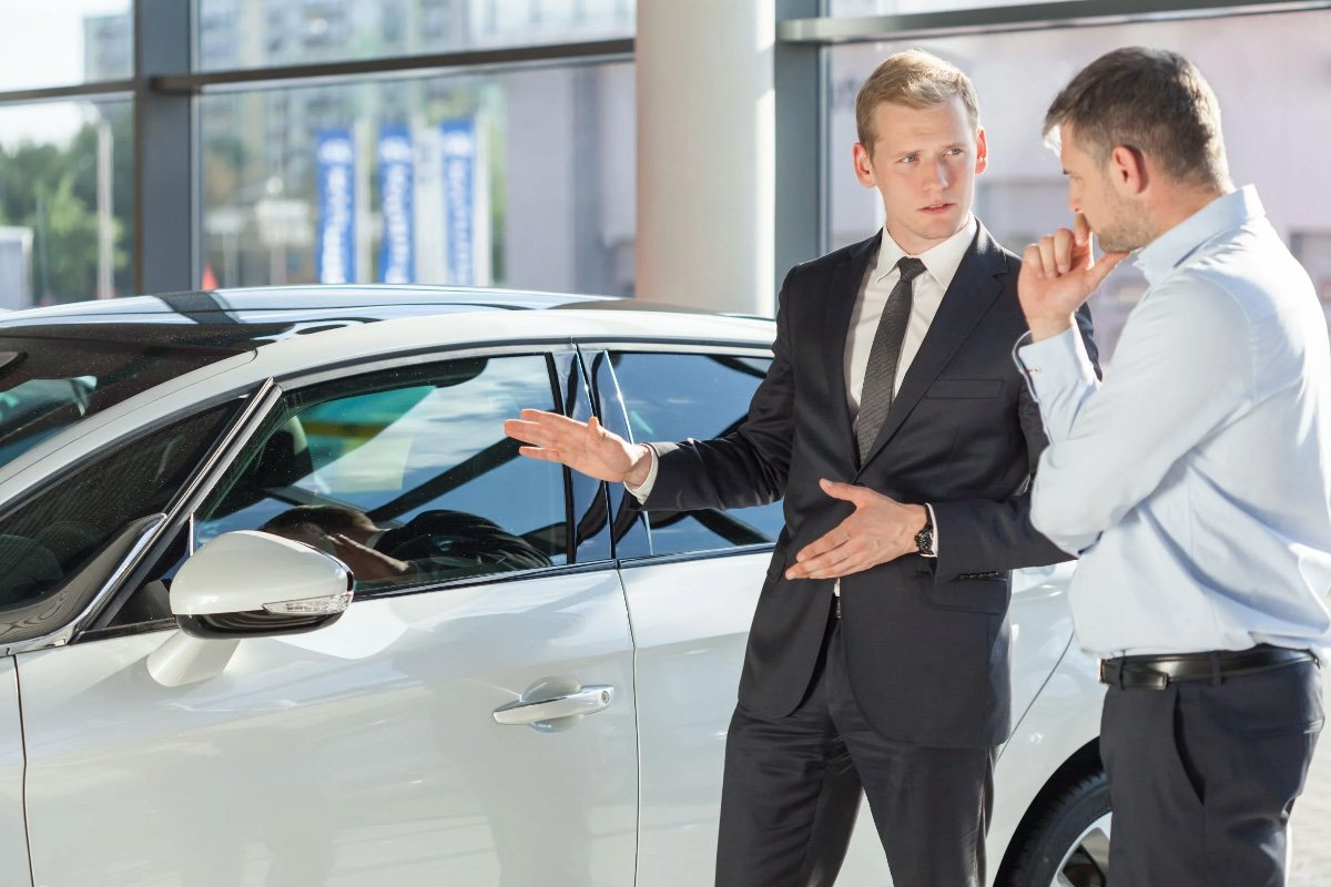 a car salesman introduces a car to customer