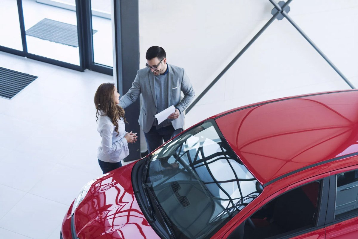 salesman and customer standing next to a red car