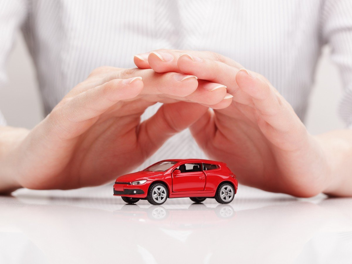 hands covering a toy car