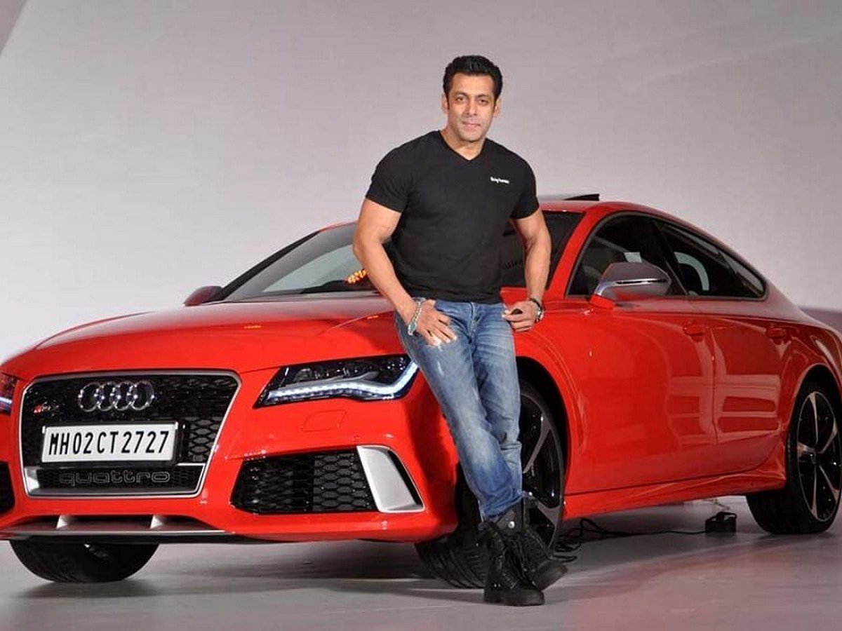 Salman Khan stands next to the red Audi RS7