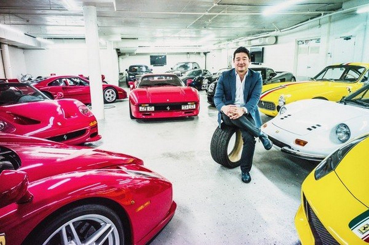 David Lee sitting on a car tyre surrounded by his car collection