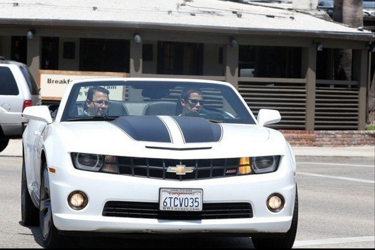 Nick and another man sitting in the white Chevy