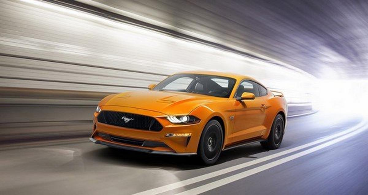 A lively orange Mustang rules the road
