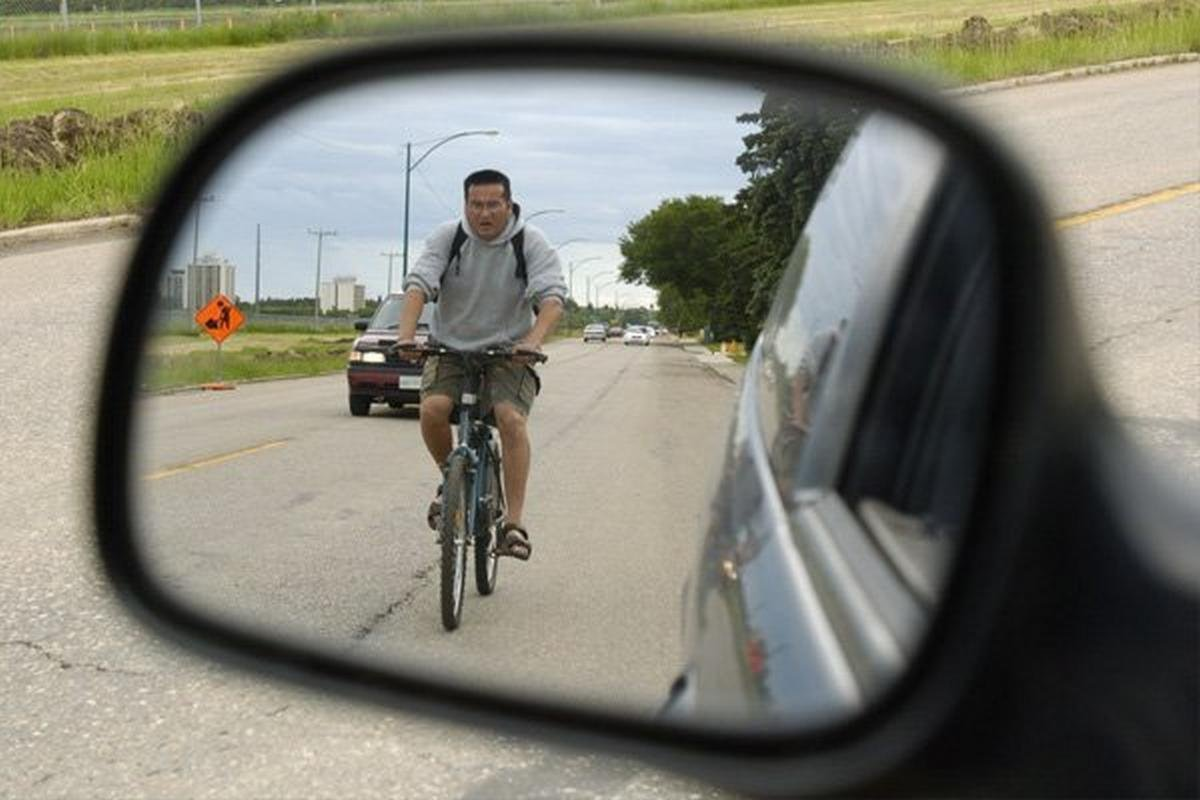 a man riding a bicycle reflected in a car's side mirror