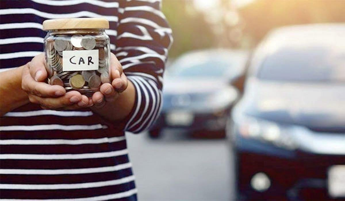 person holding a glass jar savings for car